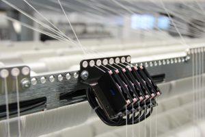 Jede Antriebselektronik verarbeitet zusätzlich noch die Daten eines lokalen Fadensensors. So können kürzeste Regelzeiten für jeden einzelnen Faden eingehalten werden. Bild: Karl Mayer Textilmaschinenfabrik