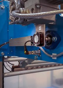 Um die Abzugsgeschwindigkeit der Folie von der Spule, die bis zu 50 m/min betragen kann, konstant zu halten, arbeitet man mit einem Tänzerarm, in dessen Drehpunkt ein Winkelsensor montiert ist. Bild: Reiner Diez